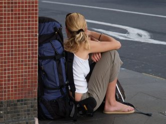 girl sitting on street with backpack