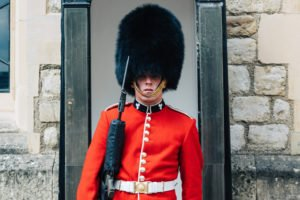 soldier in furry hat guards Buckingham Palace in London