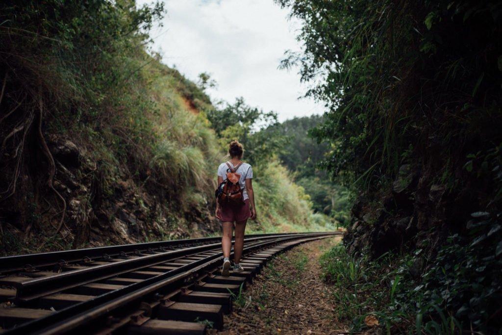 a backpacker walks railway tracks in Sri Lanka