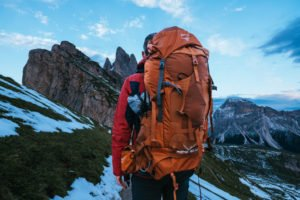 Backpacker looking at mountains with full pack