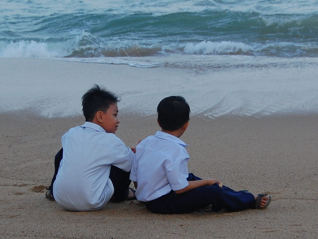 Two young boys sit on a beach